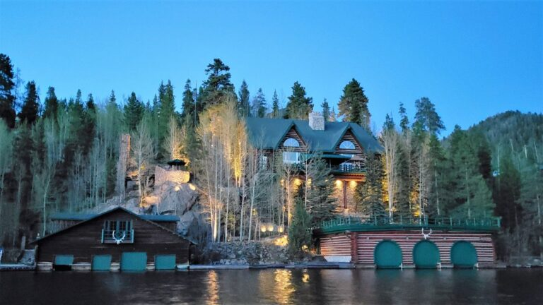Brown, white and green lakehouse with a boathouse lighted up at night 2