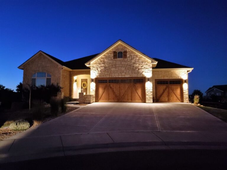 House with garage barndoors lighted at night