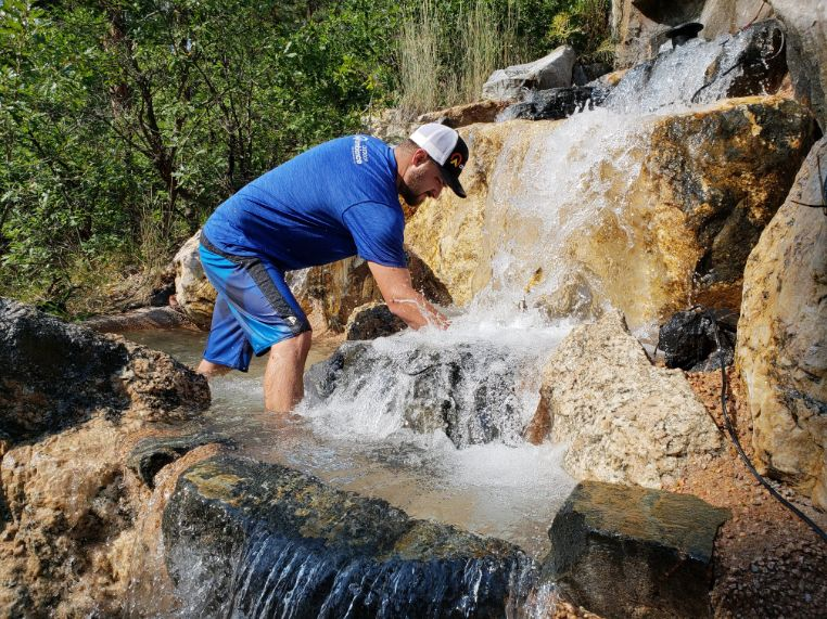 Man with hands in a waterfall