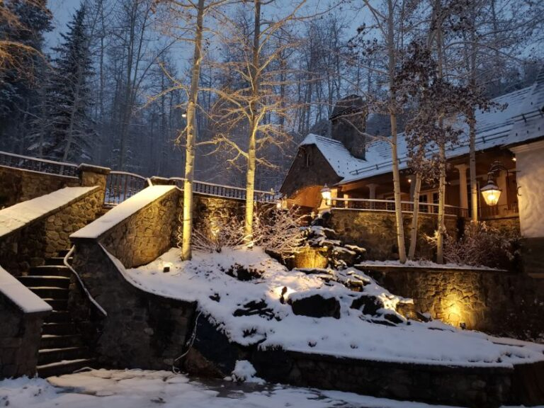 Snow covered house and steps with lights near trees