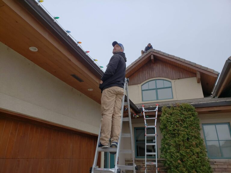 2 men with ladders hanging lights on a house