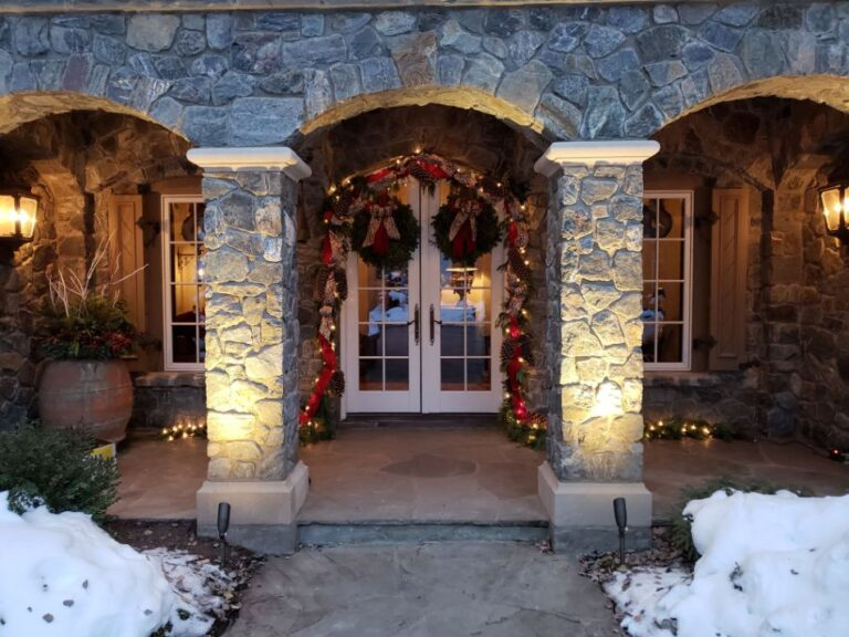 Front door archway decorated with garland and 2 wreaths 2
