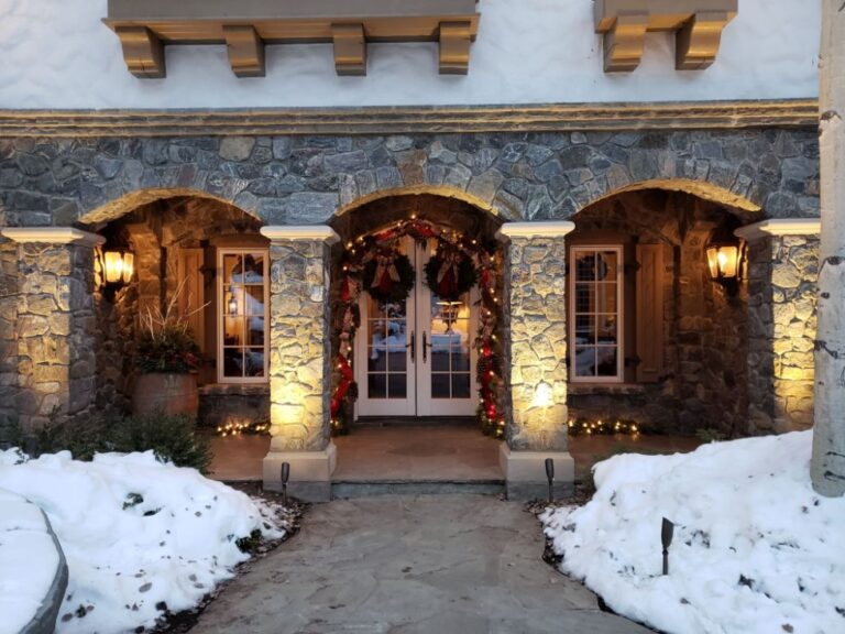 Front door archway decorated with garland and 2 wreaths