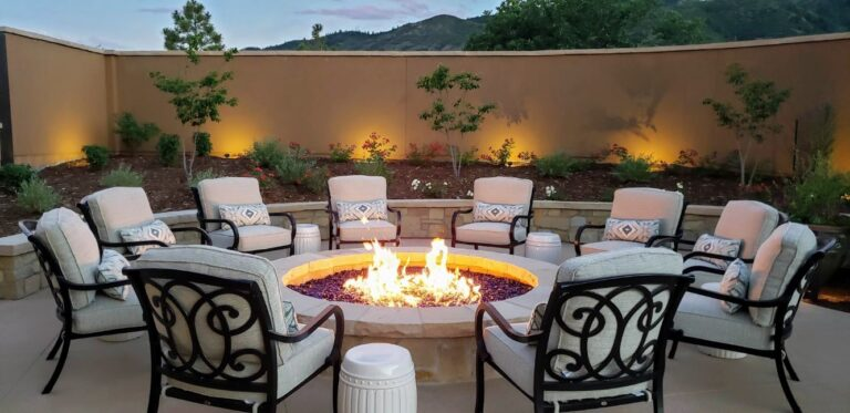 10 cream chairs around a round firepit with a lighted garden in the background