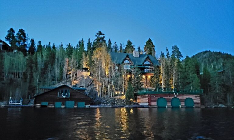 Brown, white and green lakehouse with a boathouse lighted up at night