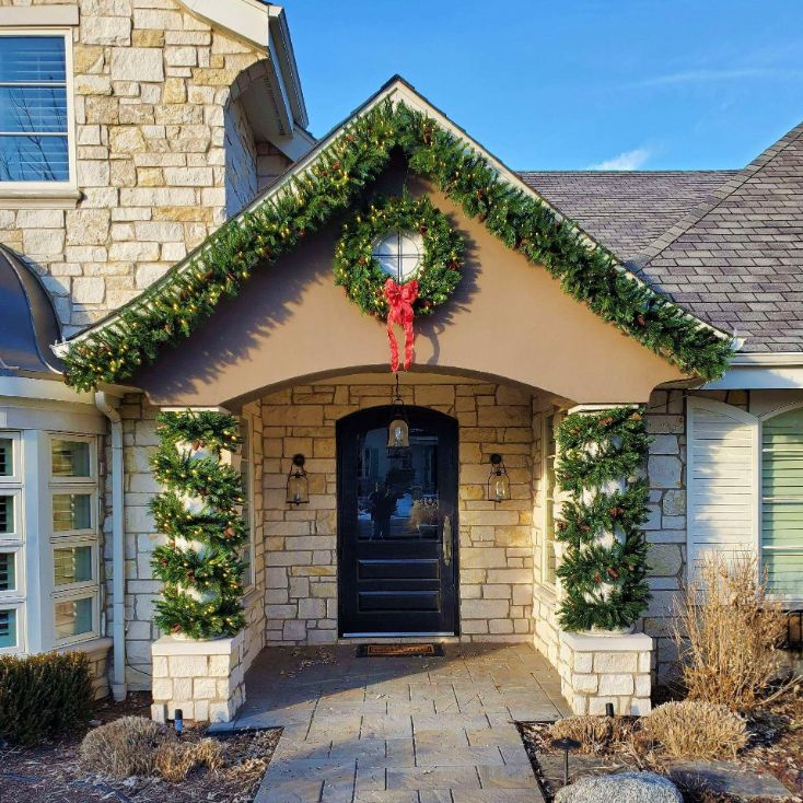 Entranceway with green garland on roofline and down pillars with a wreath in the center