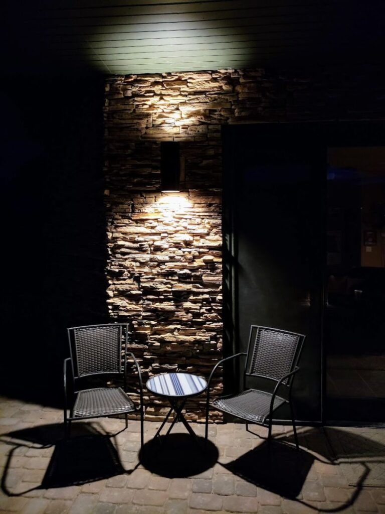 2 metal chairs and table under a light