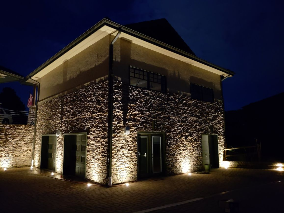 Stone house with dark green doors and lights